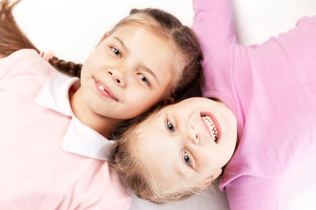 Kleine lachende meisjes met staartjes liggen in de buurt. uitzicht van boven. geïsoleerd.