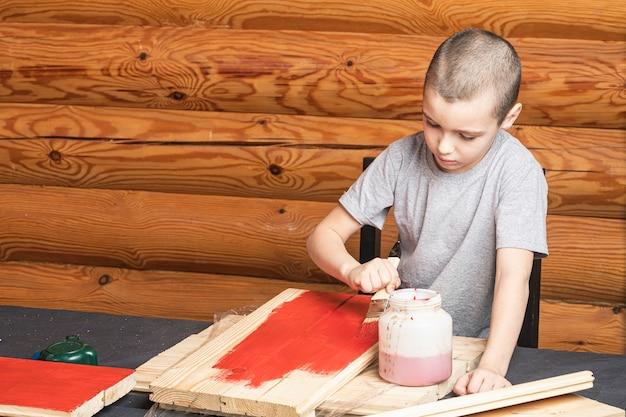Kleine lachende peuterjongen schildert een boom met een penseel in de hand in het rood