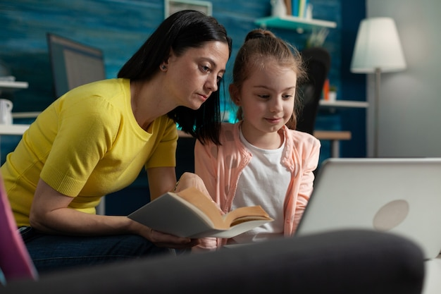 Kleine leerling die laptop gebruikt voor huiswerk en moeder helpt