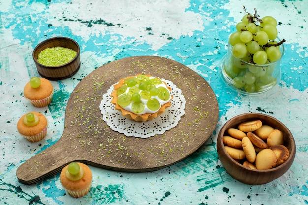 Kleine lekkere cake met heerlijke room en gesneden en verse druivenkoekjes op blauw lichtbureau, cake zoete fruitkleur