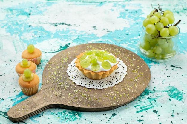 Kleine lekkere cake met heerlijke room en gesneden en verse druivenkoekjes op blauw lichtbureau, fruit van de cake het zoete suiker