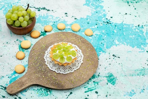 Kleine lekkere cake met heerlijke room en gesneden en verse druivenkoekjes op blauw lichtbureau, zoet suikerfruit