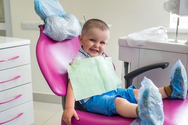 Kleine leuke jongen wacht op tandarts, in een fauteuil