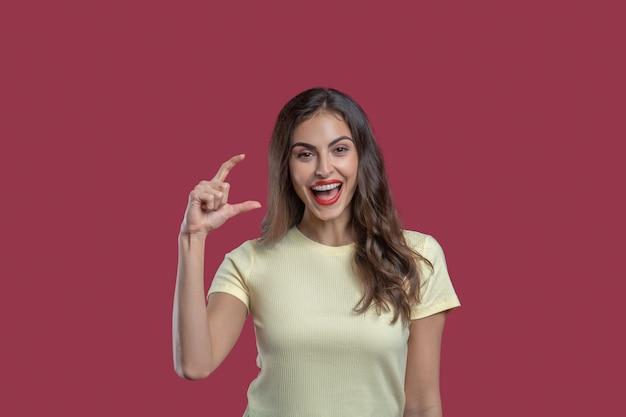 Kleine maat. jonge mooie stijlvolle vrouw lachen met open mond weergegeven: met vingers klein formaat staande op roze achtergrond