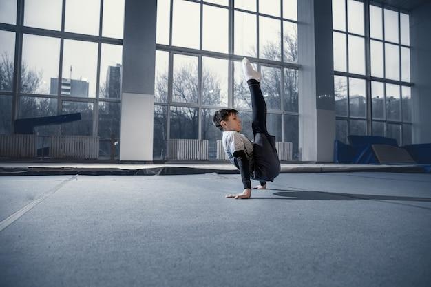 Kleine mannelijke turnster die traint in de sportschool, flexibel en actief. kaukasische fit kleine jongen, atleet in sportkleding oefenen in oefeningen voor kracht, balans. beweging, actie, beweging, dynamisch concept.