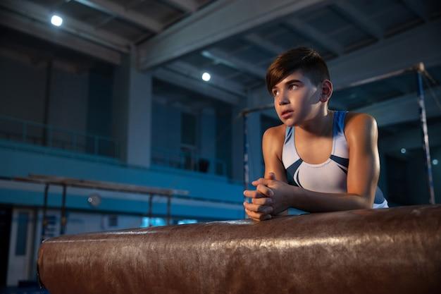Kleine mannelijke turnster training in de sportschool, flexibel en actief. kaukasische fit kleine jongen, atleet in witte sportkleding zelfverzekerd posten.