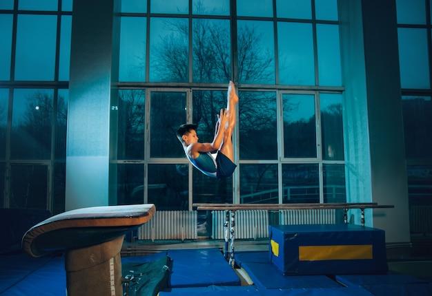 Kleine mannelijke turnster training in de sportschool, flexibel en actief