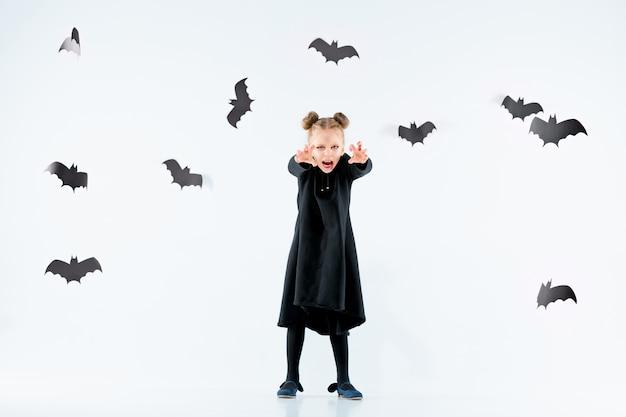 Kleine meisje heks in zwarte lange jurk en magische accessoires