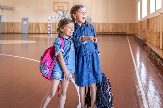 Kleine meisjes basisschoolmeisjes met rugzakken na school in de schoolgymnastiek
