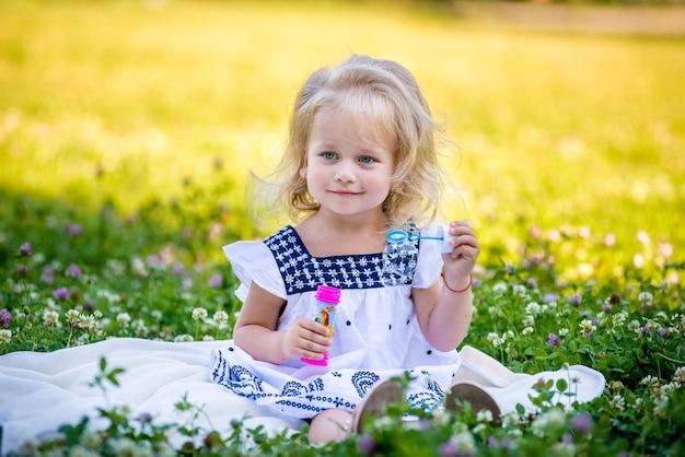 Kleine meisjes blazen bellen zittend op het gras