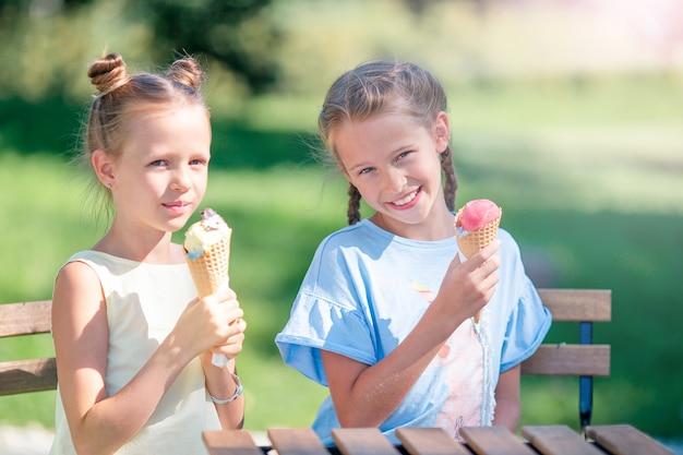 Kleine meisjes buiten eten van ijs in de zomer in openlucht café