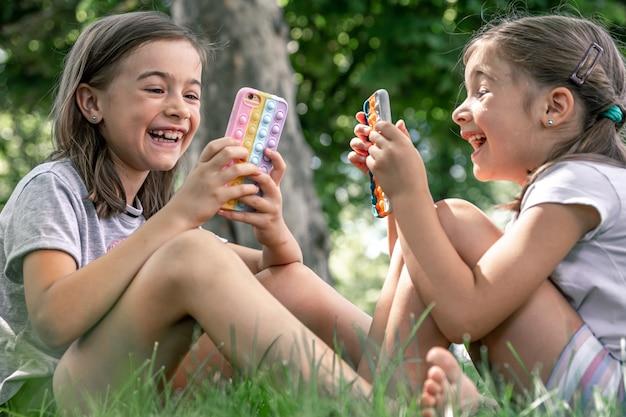 Kleine meisjes buiten met telefoons in een hoesje met puistjes pop it, een trendy anti-stress speeltje.