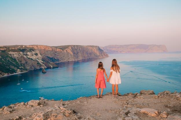 Kleine meisjes buiten op de rand van de klif genieten van het uitzicht op de bergtop bij zonsondergang