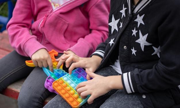Kleine meisjes die een nieuw fidgetspeeltje spelen dat populair is bij kinderen, helpt hen zich te concentreren.