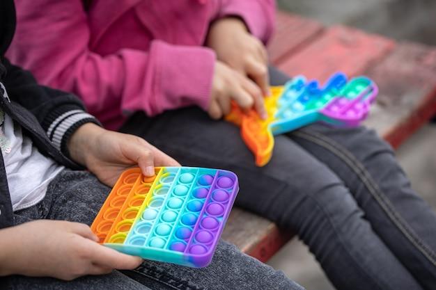 Kleine meisjes die een nieuw fidgetspeeltje spelen dat populair is bij kinderen, helpt hen zich te concentreren