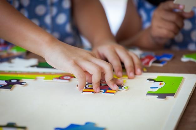 Kleine meisjes die samen een puzzel maken