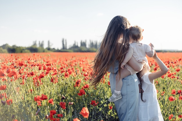 Kleine meisjes en moeder in witte jurken en kransen wandelen van papavers op papaverveld bij warme zomerzonsondergang.