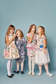 Kleine meisjes hebben plezier en spelen, vieren hun verjaardag, eten taarten en blazen bellen. meisjes in prachtige jurken op een blauwe achtergrond poseren en plezier hebben.