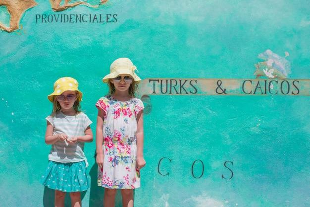 Kleine meisjes in de buurt van grote kaart van caribische eiland turks- en caicoseilanden geschilderd op de muur