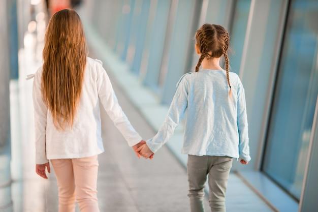 Kleine meisjes in de luchthaven in de buurt van groot raam tijdens het wachten op instappen