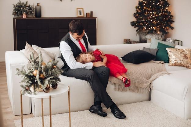 Kleine meisjes in rode jurk liggen in de buurt van de kerstboom op de knieën van haar vader