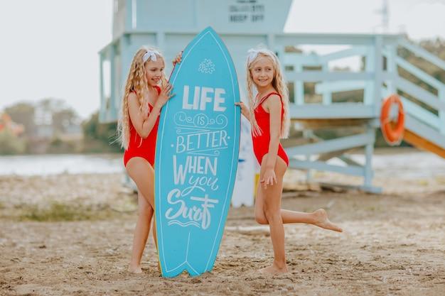 Kleine meisjes in rode zwemkleding met blauwe surfplank met citaat erop en badmeestertoren op de achtergrond