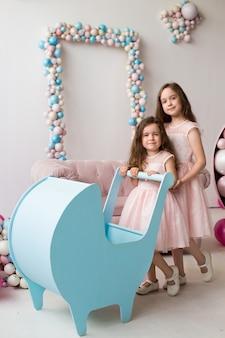 Kleine meisjes in roze jurken spelen als kleine moeders met een blauwe kinderwagen