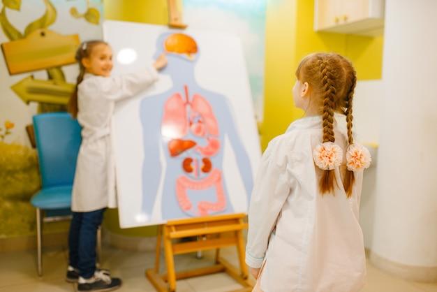 Kleine meisjes in uniform spelen dokter bij de poster met menselijke organen