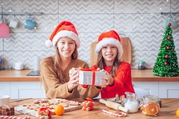 Kleine meisjes kerst peperkoek huis maken bij open haard in ingerichte woonkamer.