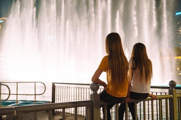 Kleine meisjes kijken naar de legendarische show van zingende fonteinen in dubai