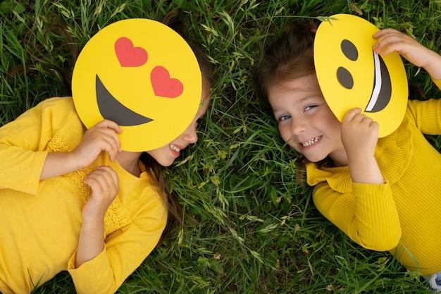 Kleine meisjes liggen op het gazon en bedekken een deel van hun gezicht met emoticons en lachen vrolijk