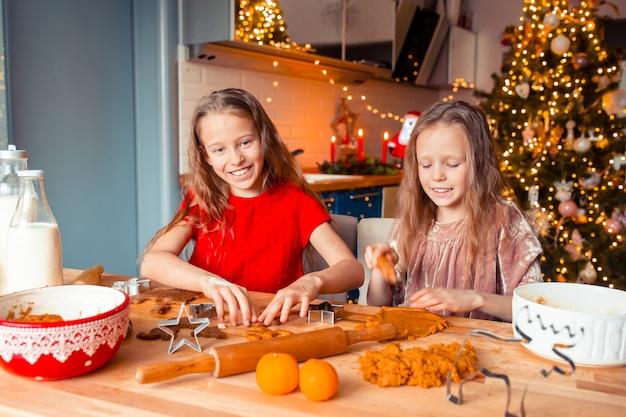 Kleine meisjes maken kerst peperkoek huis bij open haard in ingerichte woonkamer.