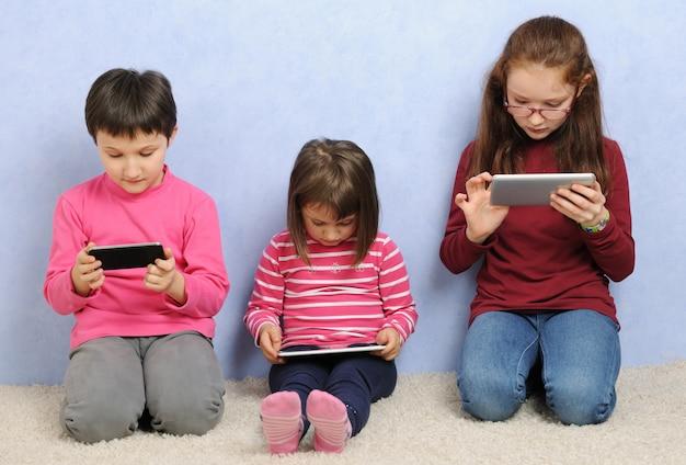 Kleine meisjes met behulp van elektronische apparaten