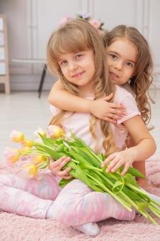 Kleine meisjes met een blanke uitstraling spelen zittend op de grond in een lichte woonkamer in scandinavische stijl met een boeket bloemen