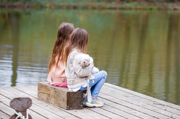 Kleine meisjes met een witte puppy. een puppy in de handen van meisjes