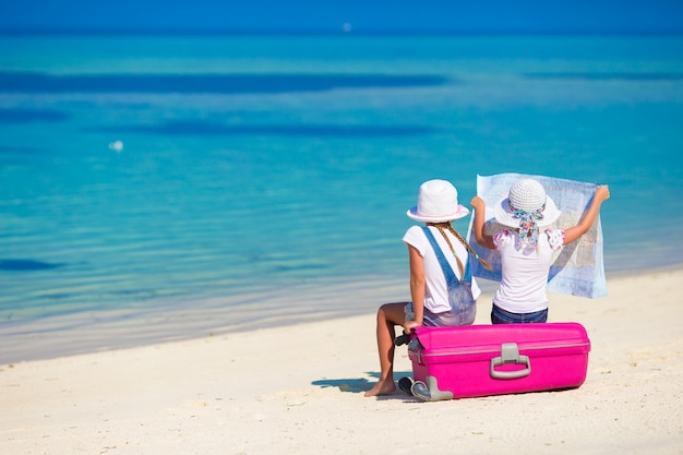 Kleine meisjes met grote koffer en kaart op tropisch strand