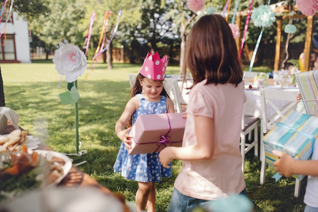 Kleine meisjes met hoed buiten in de tuin in de zomer, met cadeautjes. een feestconcept.