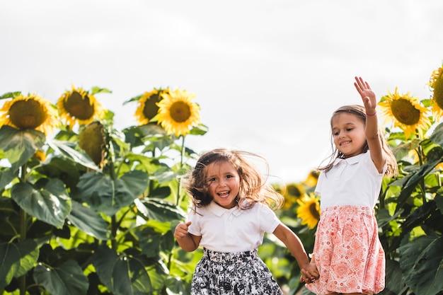 Kleine meisjes onder van een zonnebloem onder een veld met zonnebloemen in de avond. zomerconcept, seizoen van het jaar. detailopname.