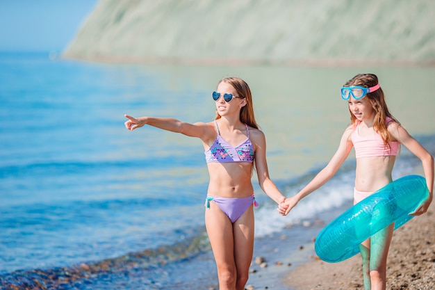 Kleine meisjes plezier op tropisch strand tijdens de zomervakantie samen spelen