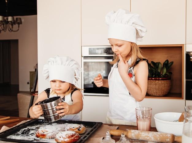 Kleine meisjes proeven suiker in de keuken in witte koksmutsen
