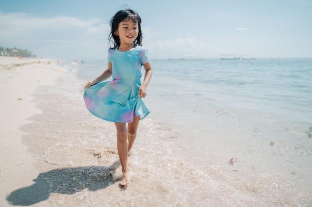 Kleine meisjes rennen en lachen op het strand