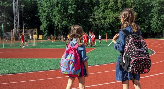 Kleine meisjes schoolkinderen met rugzakken in het stadion, kijken naar de jongens voetballen.