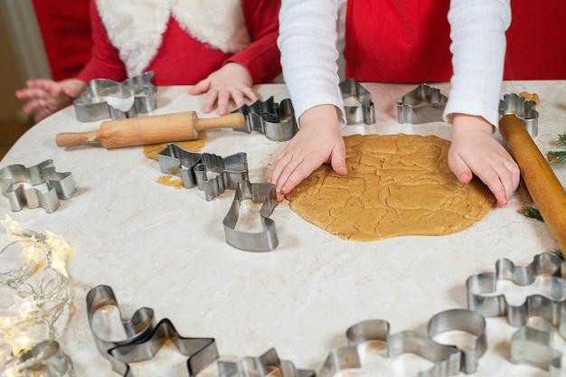 Kleine meisjes snijden alleen de handen van peperkoekkoekjes