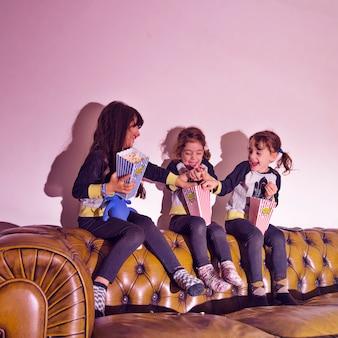 Kleine meisjes spelen met popcorn op de bank