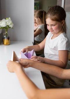 Kleine meisjes spelen thuis met origamipapier