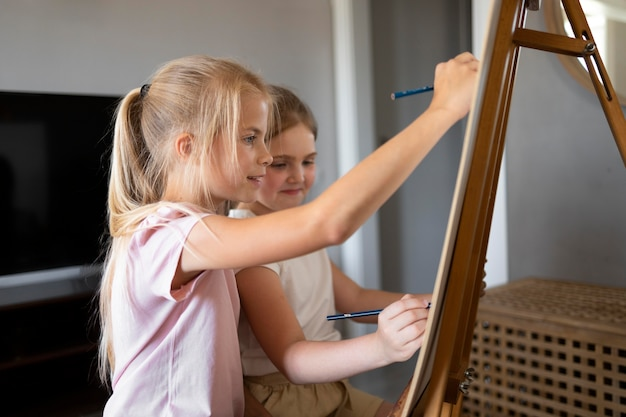 Kleine meisjes tekenen samen thuis met ezel Gratis Foto