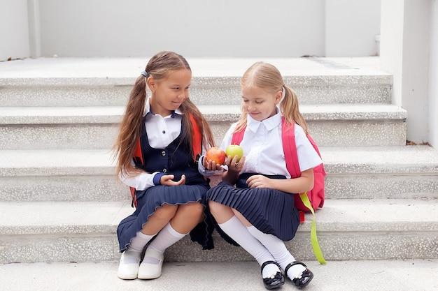 Kleine meisjes van 6-7 jaar houden een verse appel in hun handen in de open lucht. in een schoolrugzak en uniform. jeugd. terug naar school. 1 september. goedemorgen.