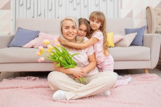 Kleine meisjes van kaukasisch uiterlijk knuffelen met hun moeder, zittend op de vloer voor de bank in een lichte woonkamer in een scandinavische stijl