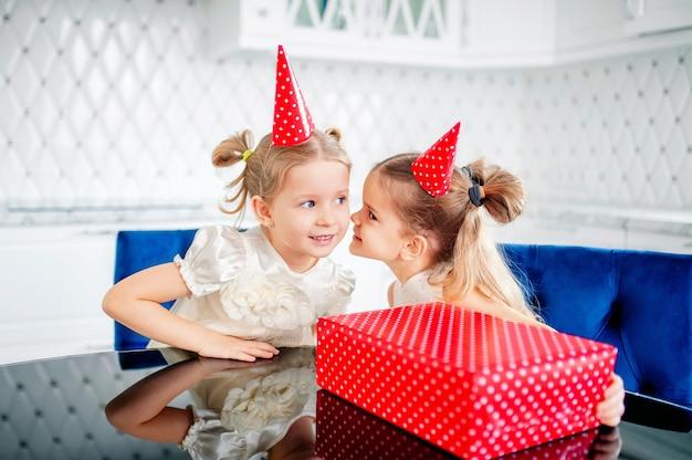 Kleine meisjes zitten aan tafel en fluisteren in hun oor een geheim in de buurt, een rood geschenk met witte stippen. verjaardag van meisje. genieten van hun verjaardagscadeautjes. uitwisseling van geschenken. vakantie