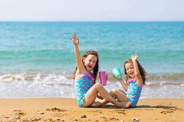 Kleine meisjes zitten tegenover elkaar, drinken uit gekleurde mooie cocktailglazen en hebben plezier. familie vakantie